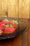 Ripe red strawberries in the water on the plate on the brown Stock Images