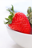Ripe red strawberries in a white ceramic bowl on a white background. Royalty Free Stock Photography