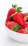 Ripe red strawberries in a white ceramic bowl on a white background. Stock Photography