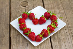 Ripe red strawberries on white plate Royalty Free Stock Image