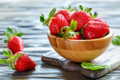 Ripe red strawberries in a wooden bowl. Stock Images