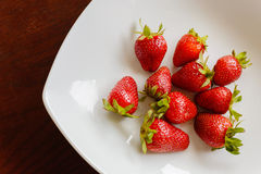 Ripe red strawberries on wooden table. Ripe red strawberries in the plate on wooden table Royalty Free Stock Photography