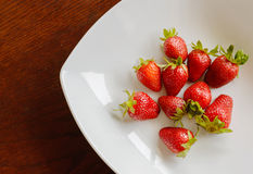 Ripe red strawberries on wooden table. Ripe red strawberries in the plate on wooden table Royalty Free Stock Photo