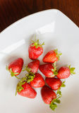 Ripe red strawberries on wooden table. Ripe red strawberries in the plate on wooden table Royalty Free Stock Photos
