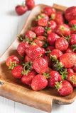 Ripe red strawberry on a tray on a white background for breakfas. Ripe large red strawberry on a tray for breakfast, on a white wooden background Royalty Free Stock Photo