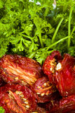 Ripe red sun-dried tomatoes with parsley. Ripe red sun-dried plum tomatoes with fresh green parsley Royalty Free Stock Photo