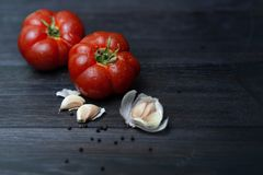 Ripe red tomato with spices on dark background stock photo