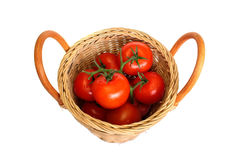 Ripe red tomatoes in a basket isolated on a white. Ripe red tomatoes in a wattled basket isolated on a white background Stock Photo