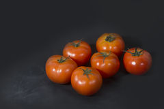 Ripe red tomatoes on black background. 6 ripe red tomatoes on black background stock images