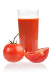 Ripe red tomatoes and glass of tomato juice. Royalty Free Stock Photo