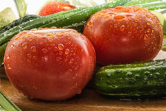 Ripe red tomatoes, green cucumbers, green onion feathers are covered with large drops of water, composition on a wooden. Ripe red tomatoes, green cucumbers Royalty Free Stock Image
