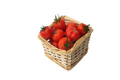 Ripe red tomatoes isolated on a white backgr. Ripe red tomatoes in a wattled basket isolated on a white background Royalty Free Stock Photography