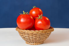 Ripe red tomatoes. In a wicker pottle royalty free stock image