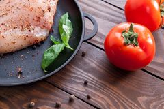 Ripe red tomatoes on a wooden table next to a frying pan on which a fresh raw chicken fillet is sprinkled with herbs and. Spices and a leaf of basil Royalty Free Stock Photos