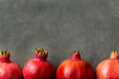 Ripe Red Vibrant Organic Pomegranates Arranged in Border on Black Stone Background Poster Greeting Card Template Banner Autumn Stock Photo