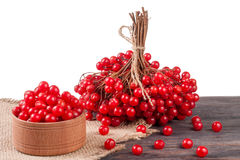 Ripe red viburnum berries in a wooden bowl on the table isolated  white background Stock Photo