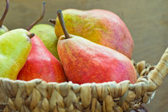 Ripe red and yellow organic pears in wicker basket on weathered wood kitchen table by window Royalty Free Stock Photography