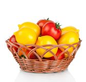 Ripe red and yellow tomatoes in wicker basket Stock Images