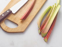Ripe rhubarb stems and some utensils  upon wooden board. Stock Images