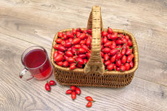 Ripe rosehip berries in a basket on a wooden background Royalty Free Stock Image