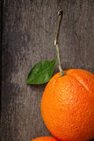 Ripe round orange with stem and leaf on wooden table Stock Photos