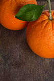 Ripe round orange with stem and leaf on wooden table Royalty Free Stock Photo