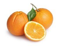Ripe round oranges with half, stem and leaf Stock Image