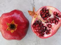 Ripe ruby red pomegranate and cut half on gray and white stone backdrop. Stock Image