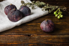 Ripe seasonal figs on wooden surface with dry herb Stock Image