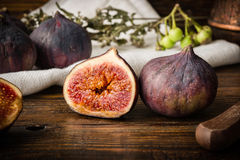 Ripe seasonal figs on wooden table with sliced one Royalty Free Stock Photography