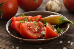 Ripe sliced tomatoes, hot chili peppers, garlic on a wooden tabl Royalty Free Stock Photos