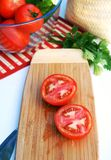 Ripe sliced tomatoes on a wooden board. Two halves of tomato on a wooden board, prepared for a healthy enriched vegetable salad, accompanied with a glass bowl Stock Photos