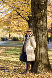 Ripe, smiling woman in autumn park at tree Royalty Free Stock Photography