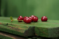 Ripe sour cherry. On a green wooden plank stock images