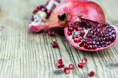 Ripe Split Pomegranate with Juicy Seeds. On wooden background stock photo