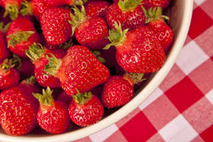 Ripe Strawberries. A bowl of freshly picked ripe strawberries sitting on a ginham tablecloth Royalty Free Stock Images