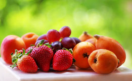 Ripe strawberries, apricot and medlars royalty free stock photos