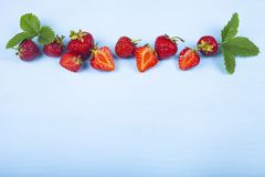 Ripe strawberries on a blue table royalty free stock photo