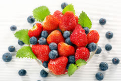 Ripe strawberries with blueberries on white background Stock Photos