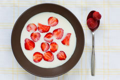 Ripe strawberries in the bowl with milk. Metal spoon aside Royalty Free Stock Photos