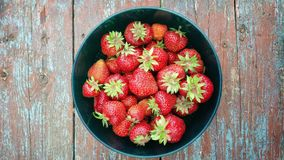 Ripe strawberries in bowl on wooden table stock photography