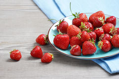 Ripe strawberries in ceramic plate at old wooden table. Stock Image