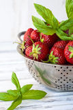 Ripe strawberries in a colander and mint leaves. Some strawberries and mint on colander. A white wooden table with a background royalty free stock photo