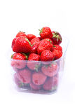 Ripe strawberries in a container. Juicy, ripe strawberries in a plastic container on a white background Stock Photos