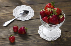 Ripe strawberries in a cup of ice cream and teaspoon on a napkin Royalty Free Stock Image