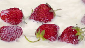 Ripe Strawberries Falling into the Milk. stock video footage