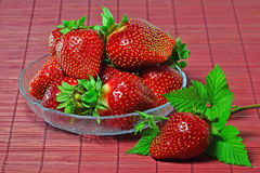 Ripe strawberries. In glass bowl over red bamboo mat Stock Photos