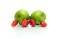 Ripe strawberries and green apples on a white background Royalty Free Stock Photo