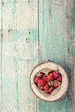Ripe strawberries in a heart carved into the wood on the old woo Stock Photo