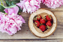 Ripe strawberries in a heart carved into the wood with pink peon Stock Photo